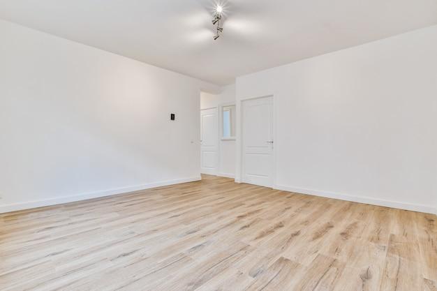 Interior de uma espaçosa sala vazia com paredes brancas e portas fechadas em apartamento moderno