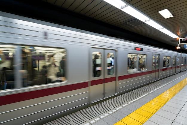 Interior de uma estação de metro de tokyo e plataforma com os assinantes do metro no tóquio, japão.