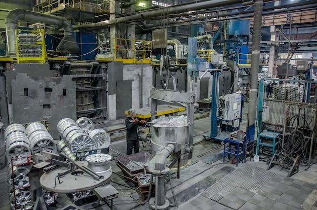 Interior de uma fundição - estação de trabalho e equipamentos para as rodas de liga leve de produção. zona industrial