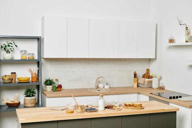 Interior de uma grande cozinha moderna com armários brancos, mesa e outras coisas