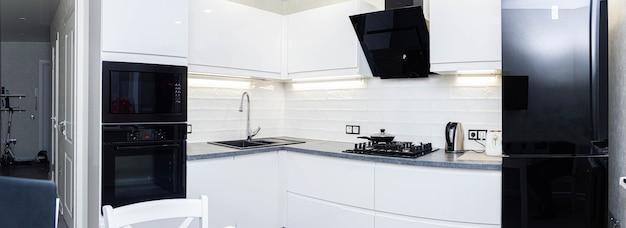 Interior de uma pequena cozinha branca com eletrodomésticos modernos