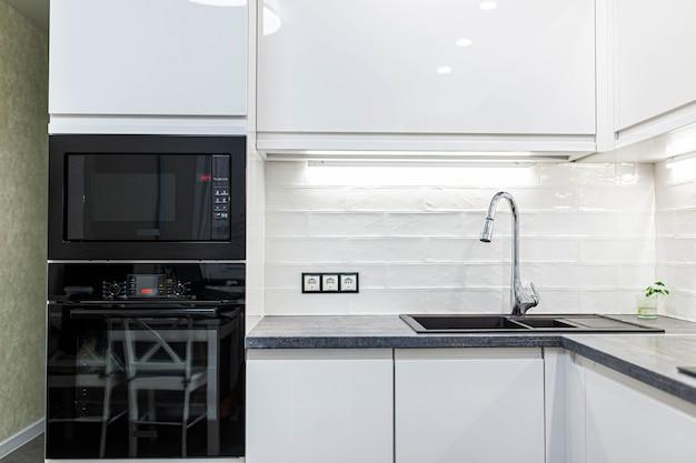 Interior de uma pequena cozinha moderna com azulejos brancos e eletrodomésticos