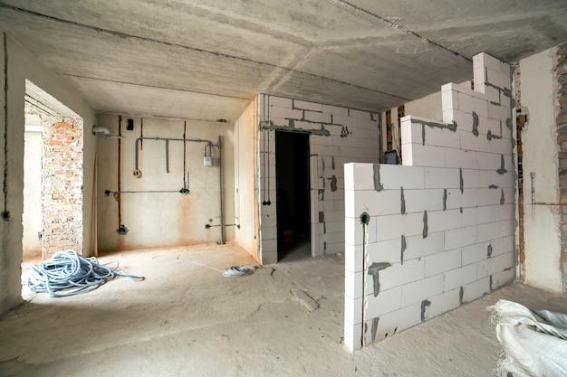 Interior de uma sala de apartamento com paredes nuas e teto em construção.