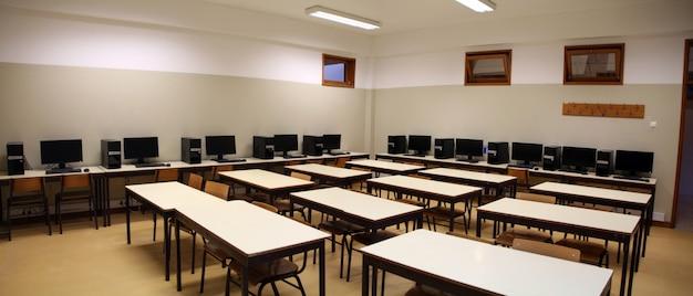 Interior de uma sala de aula com linha de computadores