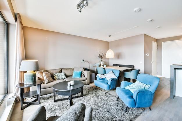 Interior de uma sala de estar elegante com sofá confortável e poltronas com almofadas colocadas no carpete ao redor da mesa em apartamento moderno