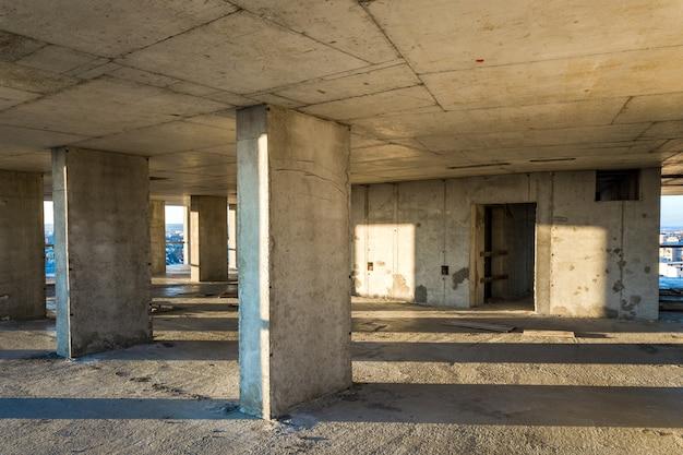 Interior de uma sala de prédio residencial de concreto com paredes nuas inacabadas