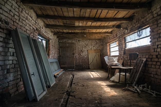 Interior do antigo celeiro na aldeia, galpão vintage construído em madeira e tijolo.