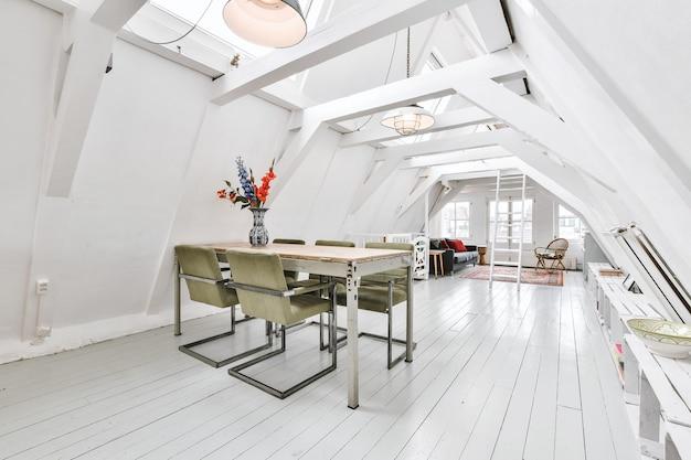 Interior do apartamento estúdio no sótão com vigas no telhado, mesa para refeições e sofá na sala de estar