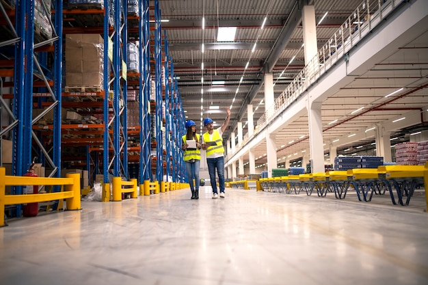 Interior do armazém de distribuição com trabalhadores vestindo capacetes e jaquetas reflexivas andando na área de armazenamento.