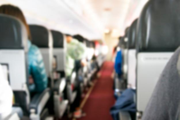 Interior do avião com foto desfocada do passageiro em assentos