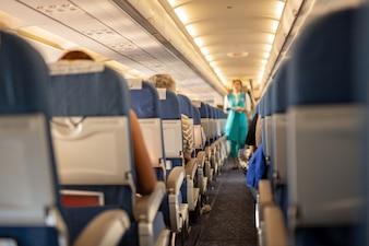 Interior do avião comercial com os passageiros em seus assentos durante o vôo.