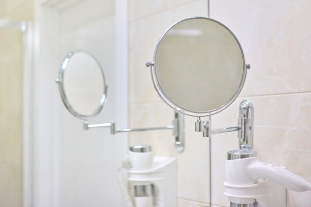 Interior do banheiro, close-up no espelho de maquiagem e secador de cabelo