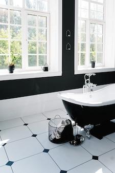 Interior do banheiro com janelas e banheira com pés