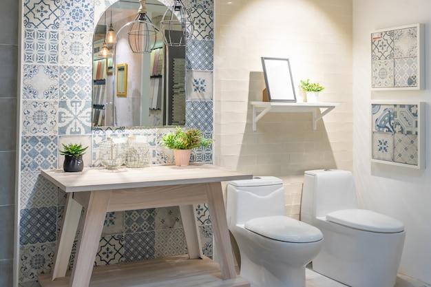 Interior do banheiro com parede branca, móveis vintage, toalhas, vaso sanitário e pia