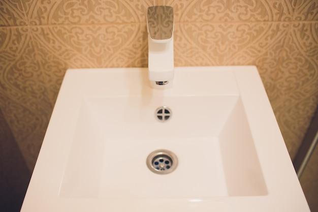 Interior do banheiro com pia e torneira branca.
