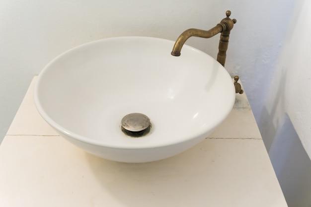 Interior do banheiro com torneira da bacia do dissipador com torneira retro do vintage.