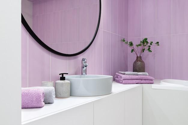 Interior do banheiro em estilo minimalista com azulejos rosa, espelho redondo acima da pia e toalhas.