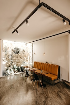 Interior do café com um sofá laranja, três mesas e três cadeiras pretas
