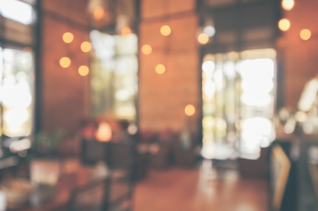 Interior do café do restaurante ou cafeteria com desfoque do cliente luz bokeh estilo vintage abstrato para fundo de exibição de produto de montagem