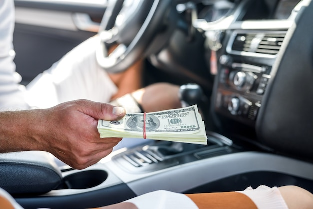 Interior do carro com mão masculina segurando o pacote de dólar close-up. imagem tonificada