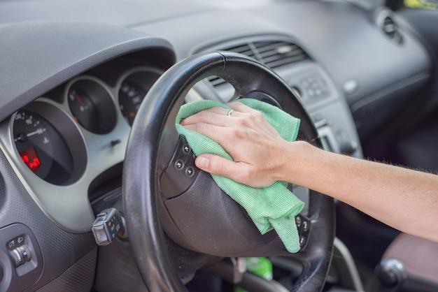 Interior do carro da limpeza da jovem mulher com pano do microfiber. detalhamento do carro.