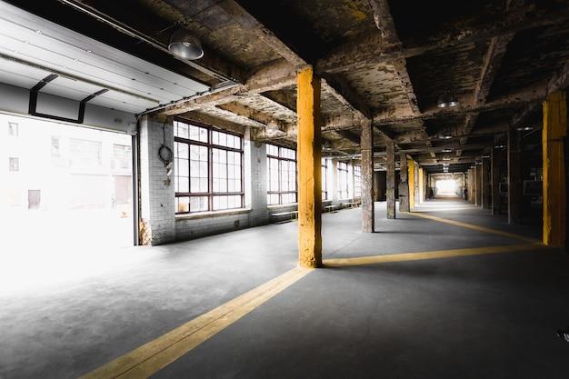 Interior do corredor da antiga fábrica abandonada com grandes janelas