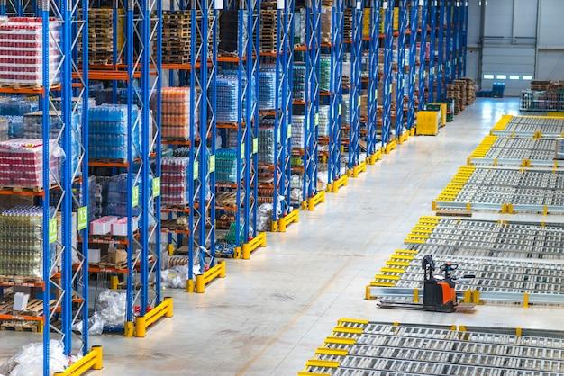 Interior do edifício do armazém de distribuição e grande área de armazenamento com mercadorias na prateleira