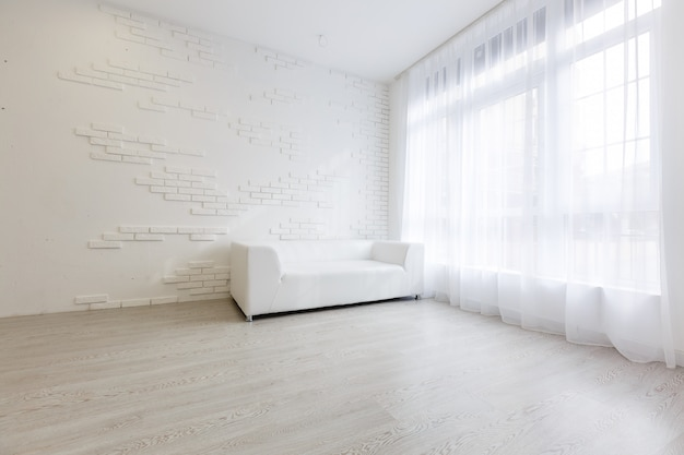 Interior do estilo moderno de sala de estar com sofá de tecido, mesa lateral e parede branca vazia