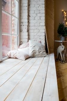 Interior do estúdio brilhante com grande janela, teto alto, piso de madeira. design de interiores do quarto de estilo loft. almofadas bege e parede de tijolos. estilo escandinavo. conceito de estilo e design.