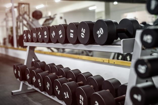 Interior do ginásio com equipamento de halteres em filas