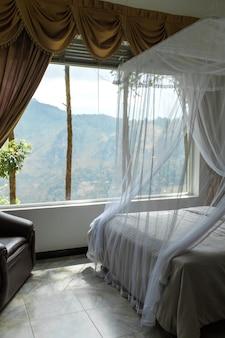 Interior do hotel com grande janela panorâmica e vista para o monte