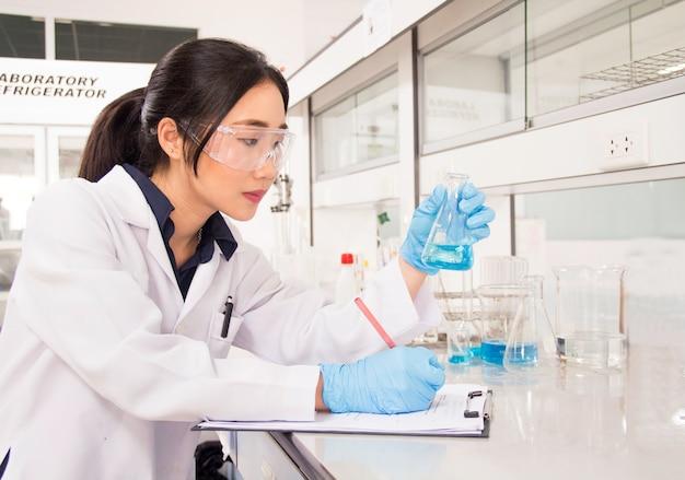 Interior do laboratório médico ou químico branco moderno limpo. cientista de laboratório que trabalha no laboratório com tubos de ensaio e relatório. conceito de laboratório com químico de mulher asiática.