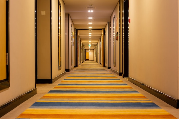 Interior do longo corredor do hotel com uma passarela listrada.