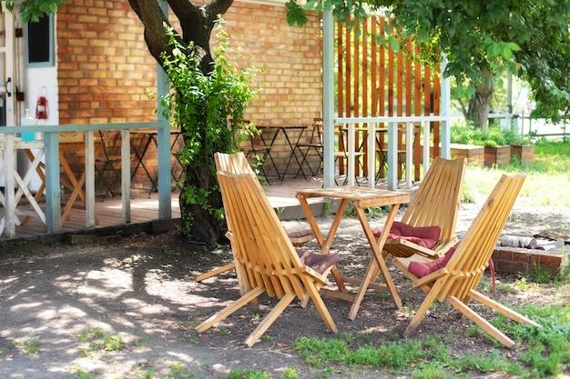 Interior do pátio do outono com mobília de jardim. espreguiçadeiras vazias e mesa na varanda da casa