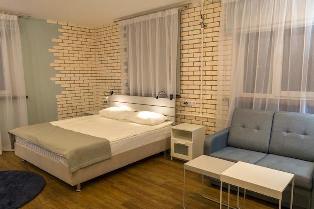 Interior do quarto, cama de casal, sofá e janelas grandes.