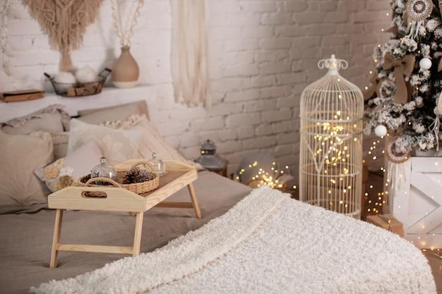 Interior do quarto com bandeja de madeira na cama com enfeites de natal