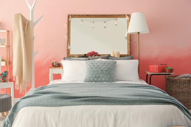 Interior do quarto com cama confortável perto da parede rosa