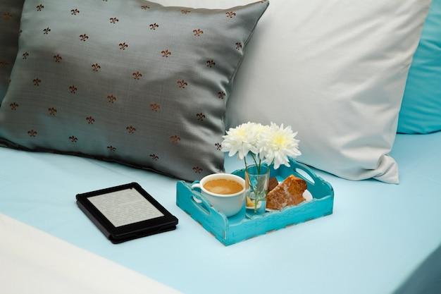 Interior do quarto com cama, mesa de cabeceira, café da manhã na bandeja e leitor eletrônico