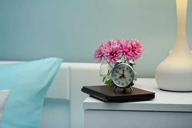 Interior do quarto com cama, mesa de cabeceira, relógio
