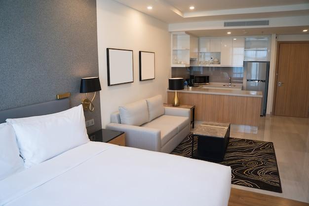 Interior do quarto de hotel com área de quarto, espaço de estar e cozinha