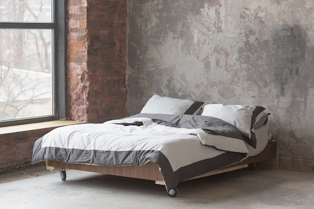 Interior do quarto em estilo loft com cama grande, design cinza, textura de tijolo e parede de concreto