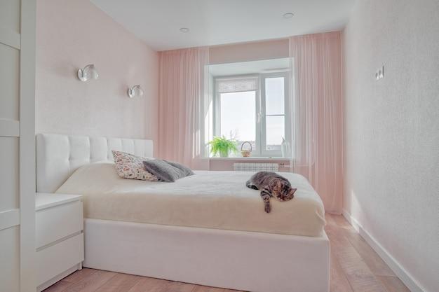 Interior do quarto em tons de rosa com conjunto de almofadas na cama em frente à janela