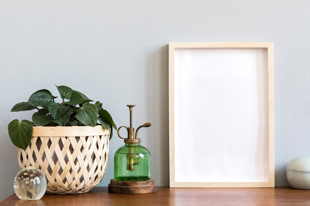 Interior do quarto escandinavo com moldura para fotos na prateleira de bambu marrom com lindas plantas em diferentes potes de hipster e design