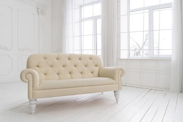 Interior do quarto espaçoso vazio com sofá de couro vintage na janela, parede branca e chão