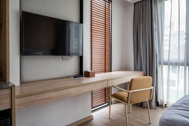 Interior do quarto projetado em estilo aconchegante de madeira. mesa e cadeira de madeira com luz do sol através da cortina