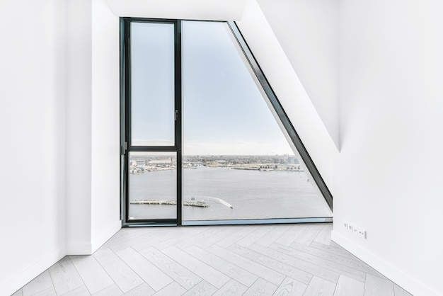Interior do quarto sem mobília com piso em parquet e paredes brancas e janela de parede em apartamento de luxo