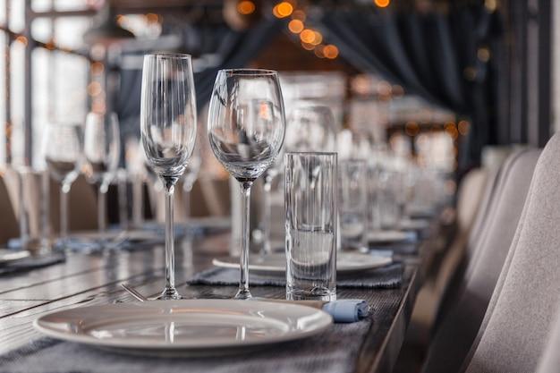 Interior do restaurante, servindo vinho e copos de água, pratos, garfos e facas em guardanapos têxteis fica em uma linha na mesa de madeira cinza vintage
