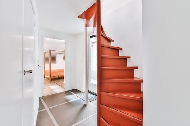 Interior do sótão claro com corrimão e escadas contra janela em casa moderna