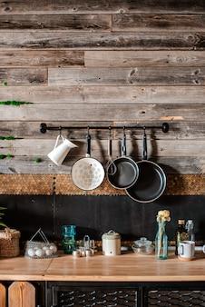 Interior e design de cozinha moderna em estilo rústico. no fundo, há uma parede de pranchas de madeira.