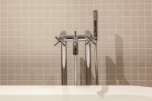 Interior e design do moderno banheiro e banheiro, itens no banheiro secador de cabelo, espelho, roupão de banho, banheira, pia, torneiras de água